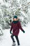 Happy woman walking through a snowy forest royalty free stock images