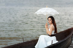 Happy Woman with Lace Parasol in an Old Wooden Boat Royalty Free Stock Images