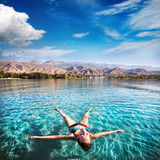 Happy Woman in lake. Woman laying like a star in Issyk Kul lake at mountains background in Kyrgyzstan, central Asia Stock Photography