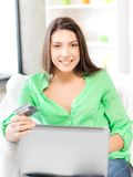 Happy woman with laptop computer and credit card Stock Photos