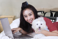 Happy woman with laptop and dog on bed Royalty Free Stock Photo