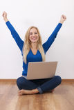 Happy woman with laptop. Excited woman with laptop sitting on floor Stock Images