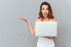 Happy woman with laptop holding copy space on palm Royalty Free Stock Photography