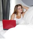 Happy woman with laptop at home. Young happy woman with laptop at home royalty free stock photography