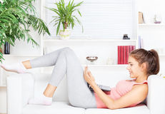 Happy woman with laptop lying on the sofa Royalty Free Stock Photo