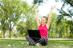 Happy woman with laptop on nature Stock Images