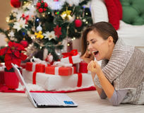 Happy woman with laptop near Christmas tree