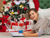 Happy woman with laptop near Christmas tree Royalty Free Stock Photography