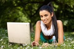 Happy woman with laptop in park Royalty Free Stock Photos