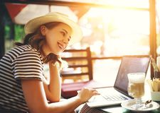 Happy woman with laptop in summer cafe stock photography