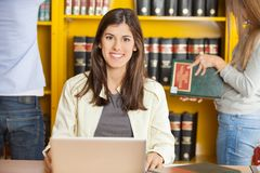 Happy Woman With Laptop At University Library. Portrait of happy young women with laptop while students standing in background at university library stock photography