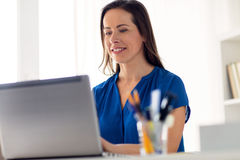 Happy woman with laptop working at home or office. Business, people and technology concept - happy smiling woman with laptop computer working at home or office Royalty Free Stock Photo