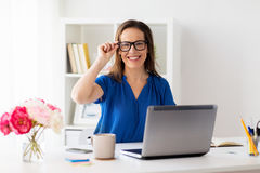 Happy woman with laptop working at home or office. Business, vision and people concept - happy smiling woman with laptop computer working at home or office Royalty Free Stock Photo