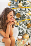 Happy woman with latte macchiato sitting near christmas tree Royalty Free Stock Image