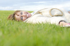 Happy woman laughing. Color portrait photo of a mature woman in her forties laying down on her back on the green grass and laughing toward the camera Royalty Free Stock Photo
