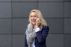 Happy woman laughing and chatting on her mobile. Happy stylish blond woman laughing and chatting on her mobile phone as she stands in front of a grey wall in royalty free stock photos