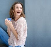 Happy woman laughing with a cup of coffee in hand