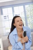 Happy woman laughing with hairbrush in hand. Happy woman acting as pop star, singing to hairbrush as microphone, laughing, having fun Stock Photography