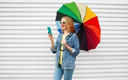 Happy woman laughing with smartphone having video call. Holds colorful umbrella on white background stock image