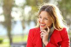 Happy woman laughing warmly clothed in winter. Portrait of a happy woman laughing warmly clothed with a red jacket in a park in winter Royalty Free Stock Photography