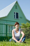 Happy  woman  on lawn in front of  home Royalty Free Stock Images