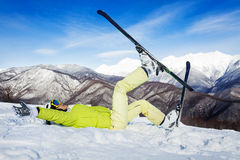 Happy woman lay in snow and lift legs with ski Stock Photo