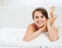 Happy woman laying in bed Stock Image