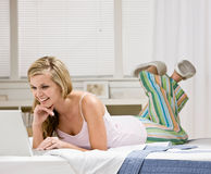 Happy woman laying on bed in bedroom using laptop Royalty Free Stock Photography