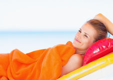 Happy woman laying on chaise-longue. Happy young woman laying on chaise-longue stock images