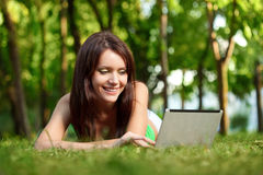 Happy woman laying on grass with laptop Stock Photography