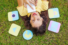 Happy woman laying on grass surrounded by app icons. Woman using smart phone while lying down on a grass. Funny paper icons of functions appear around her Royalty Free Stock Photos