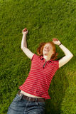 Happy woman laying on green grass. A joyful young woman laying on green summer grass with hands spread and a smile on her face Royalty Free Stock Photo