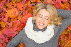 Happy woman laying in leafs and enjoying her time Royalty Free Stock Photo