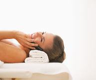 Happy woman laying on massage table and talking mobile phone Stock Photography