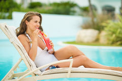 Happy woman laying on sunbed and drinking cocktail Stock Photos