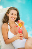 Happy woman laying on sunbed enjoying cocktail Royalty Free Stock Image