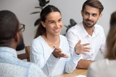 Happy woman leader coach mentor talking to employees at meeting. Happy friendly women team leader coach mentor talking to employees group at office meeting stock images