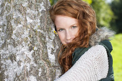Happy woman leaning against a birch tree. Outdoor Stock Image