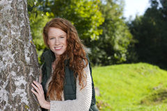 Happy woman leaning against a birch tree. Outdoor Stock Photography