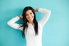 Happy woman leaning against a blue wall Royalty Free Stock Photography
