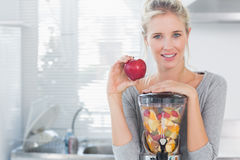 Happy woman leaning on her juicer full of fruit and holding red apple Stock Images