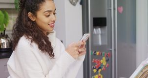 Happy woman leaning on kitchen counter using her mobile phone 4K 4k stock footage