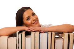 Happy woman leaning on pile of books excited of new knowledge. Stock Image