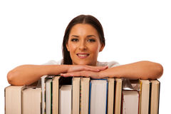 Happy woman leaning on pile of books excited of new knowledge. Stock Photos