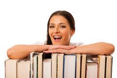 Happy woman leaning on pile of books excited of new knowledge. Stock Photo
