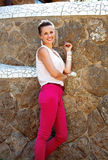 Happy woman leaning on trencadis decorated wall in Park Guell Stock Image