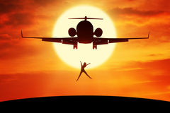 Happy woman leaps on the hill under airplane. Silhouette of attractive woman enjoy freedom and jumping on the hill under plane flying on the sky Stock Image