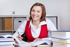 Happy woman learning at her desk Royalty Free Stock Image