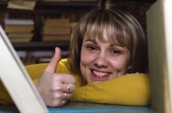 Librarian. Happy woman a librarian is looking through a bookshelf in a library and is showing a thumbs up stock image