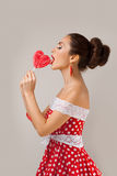 Happy Woman Lick Red Lollipop. Pin-up retro style Stock Photo